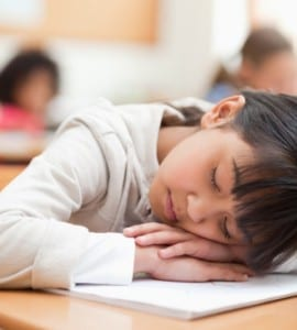 Elementary student taking a nap on her desk