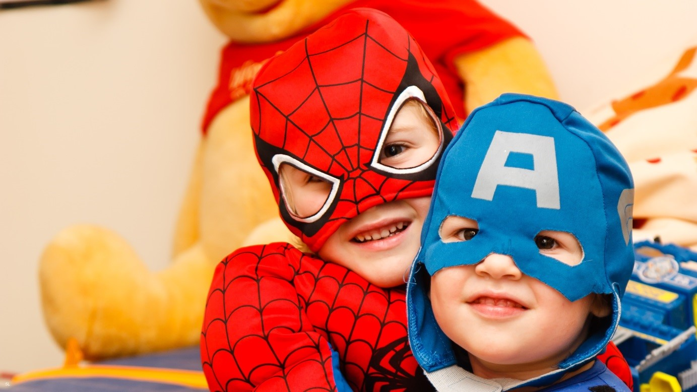 the right time to ask for help is when you realize that you could use some. Kindergarten is one of the places that can offer help. Two children in superhero costumes.