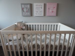 An ordinary white crib with grey and white sheets