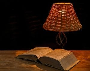 A lamp and an open book on a table.