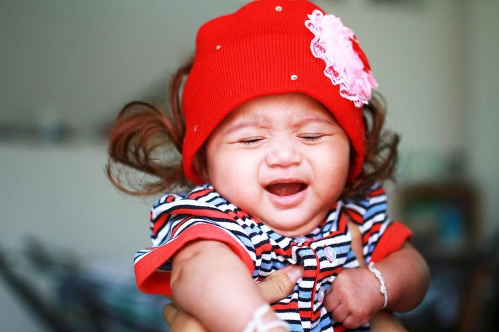 A baby girl wearing a red cap, crying.