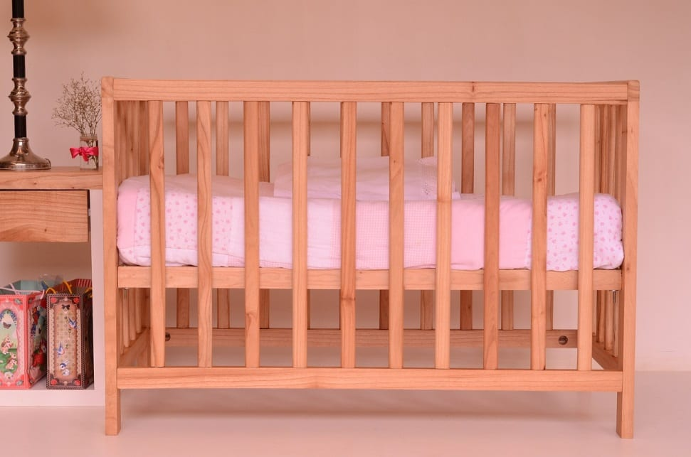 A picture of a wooden baby cot with pink sheets.