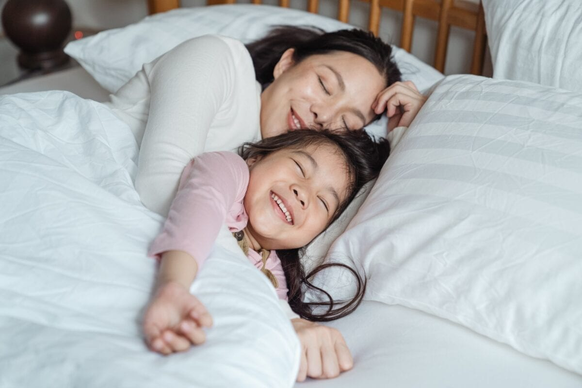 mom and child happy resting in bed